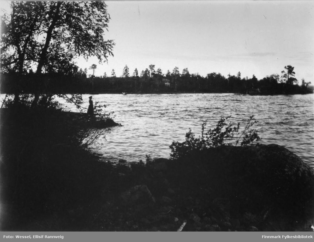 Et landskapsbilde fotografert fra Pasvik. Bak bildet står teksten 'Fra Mennikafoss i Pasvik mellom fossens to fald.' Ved stranden står en kvinne. På andre siden elvaen ligg det en hytte.