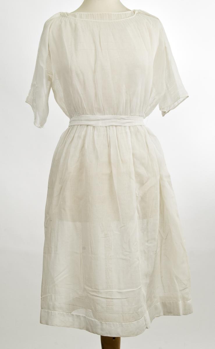 Hvit forseggjort kjole med rund utringning. Biser ned fra halsen, Kimonoerm. Strikk i livet og belte. Broderier.
