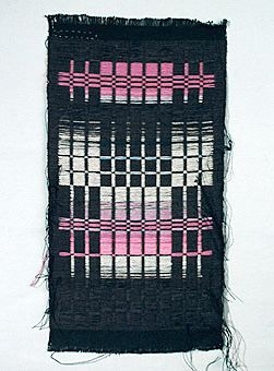 Vävprov i lin och ull vävt i plattväv. Varp i svart lingarn. Botteninslag och mönsterinslag i kulört ullgarn. Brunt botteninslag med plattvävsstaplar i natursvart, naturgrått och rosa som går över till lila.