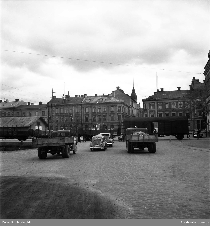 Stadsvy från 1950 tagen från Hamngatan söderut mot korsningen Sjögatan-Tullgatan. Vägen spärras av ett godståg på väg in eller ut från dåvarande Magasinsgatan mellan magasinshusen som numera (2015) är Kulturmagasinet. Till vänster skymtar den numera igenfyllda hamnbassängen.
