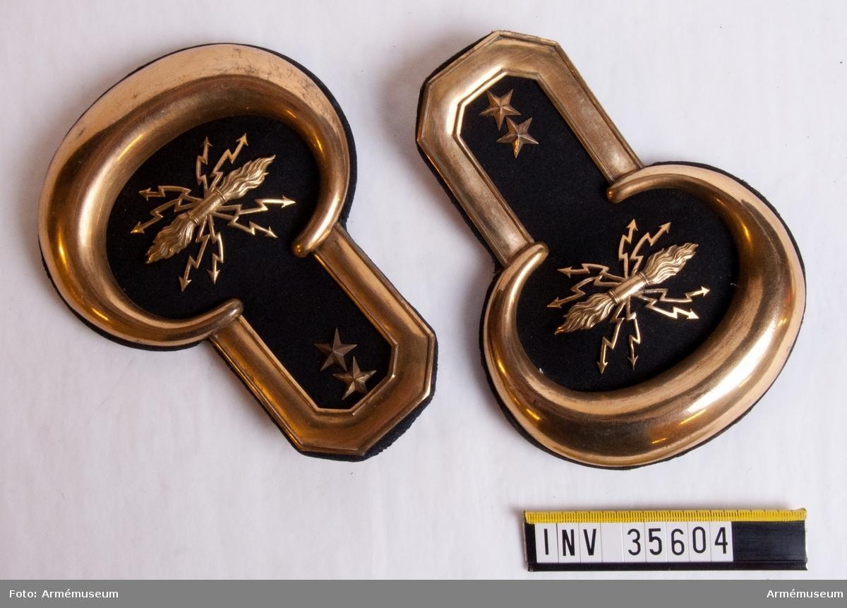 Grupp C I. Ett par epåletter av svart ylletyg med gulmetallfattning runt emblem och två stjärnor. På baksidan en metallkrok märkt Morell & Co.