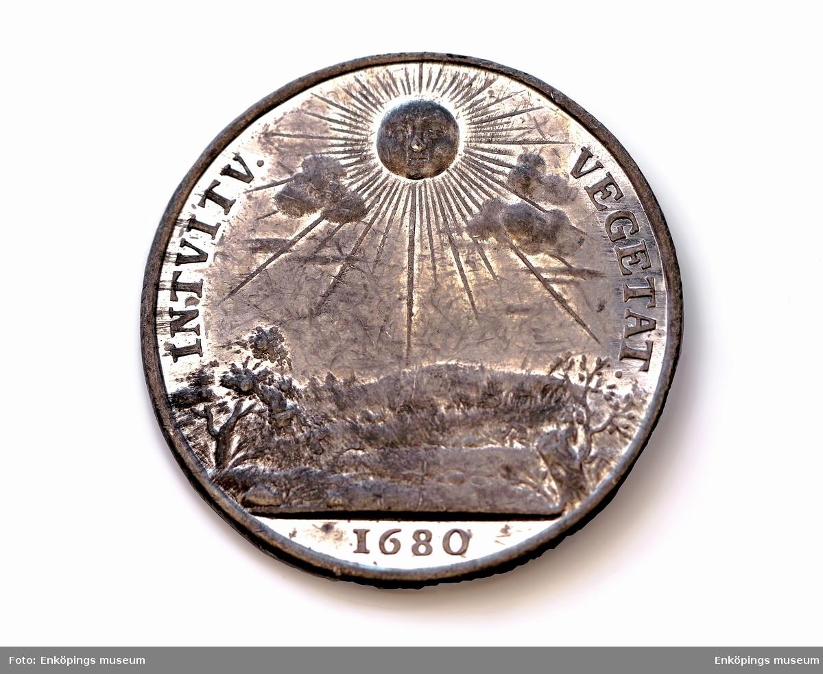 """Gjuten medalj i tenn överdragen med vitmetall. På framsidan profilbild av Carl XI med texten: """" CAROLUS XI D G REX SVEC"""". På baksidan lyser en sol över ett landskap där man kan urskilja träd, jägare med hund, stugor, man som slår gräs. Texten lyder """" INTVITV VEGETAT 1680"""".   Avgjutningar av medaljer i Grönsösamlingar."""