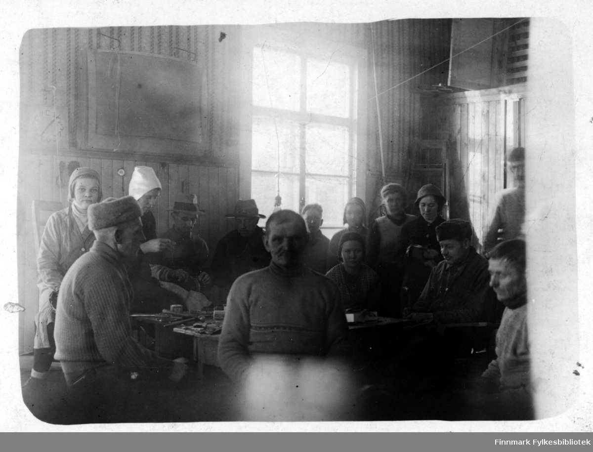 En gruppe evakuerte fra Petsjenga arbeider med kartangerproduksjon i et skolelokale. Kvinner og eldre menn sitter rundt pulter i et klasserom og jobber.