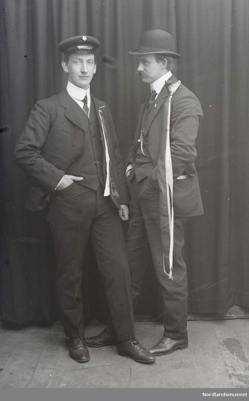 Portrett. To menn, begge står. Begge har på seg 17. mai- sløyfer festet i jakkens venstre skulderparti. Den ene er sannsynligvis russ, han er også med på NM 8243:119 og NM 8243:130. Begge er også med på NM 8243:115.
