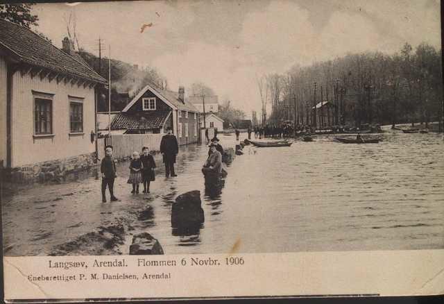 Flommen i Barbuelva 6. Novbr. 1906.  Elven i h. side. Barn og voksne på veien tv. og sitter på stabbesteinene. Prammer og mennesker i bakgrunnen. Veien er Vestlandske hovedvei.