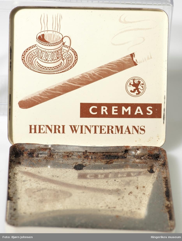 På fronten av  lokket: A- dampende sigarillo, løve med hellebard i en oval logo med en stilisert krone over; B - stilsvarende sigarillo, en mindre logo og en kaffekopp med skål,  fylt med rykende varm kaffe.