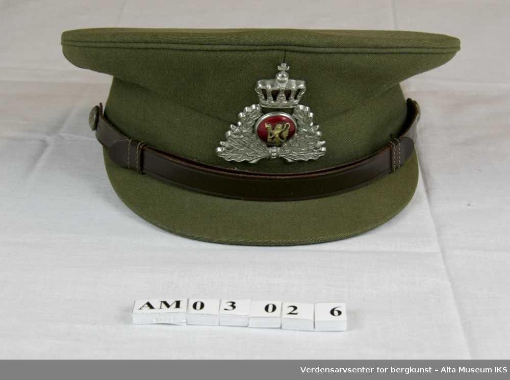 Med emaljert merke og stofftrukket skygge. Ekeløvsornament med den norske løve og krone. Militærgrønn, luemerke i rødt, gull- og hvitmetall.
