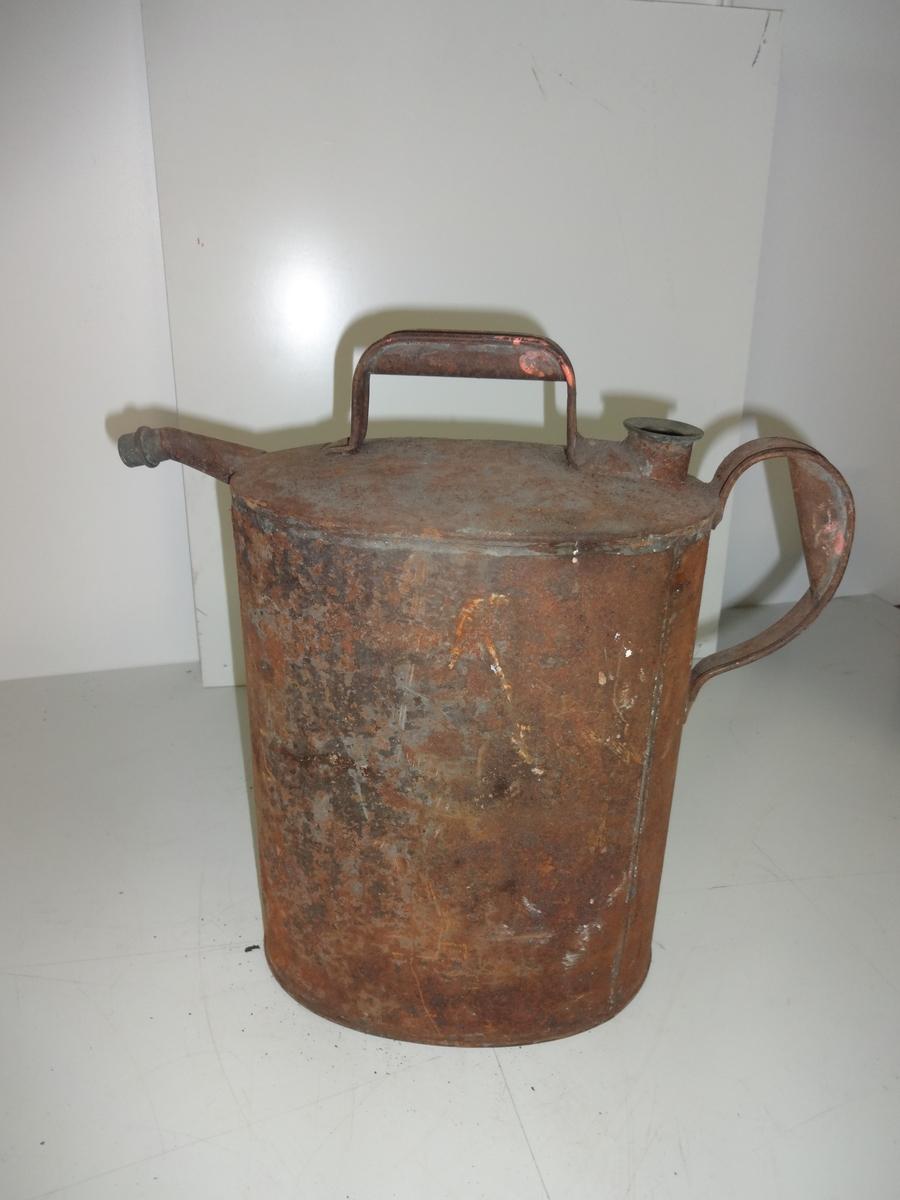 Oljekanne brukt til transport og påfylling av olje/parafin på fyr eller fyrlykter. Kannen har to håndtak. Kannen er oval. På toppen har kannen tut som på kaffekanne og håndtak. Kannen er brun av rust, men hel. Den har vært svart.