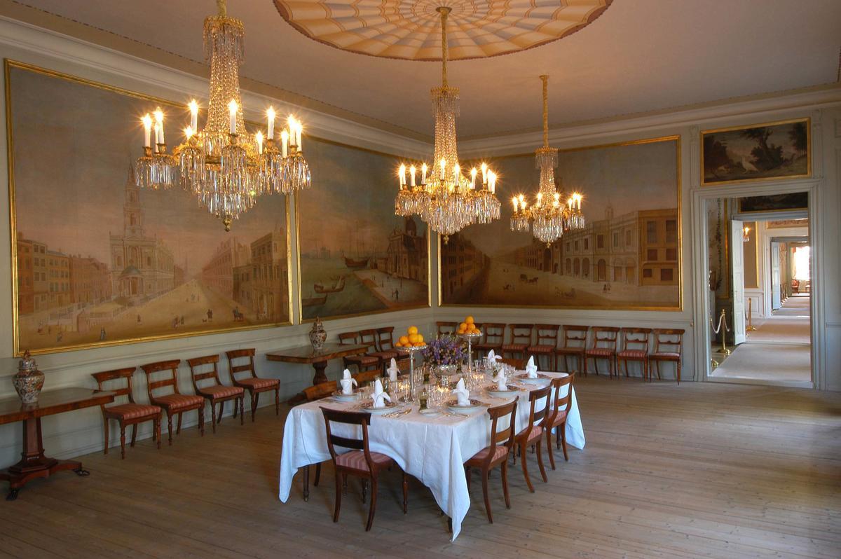 Spisesalen i Stiftsgården, med dekket bord, veggmalerier og tente lysekroner