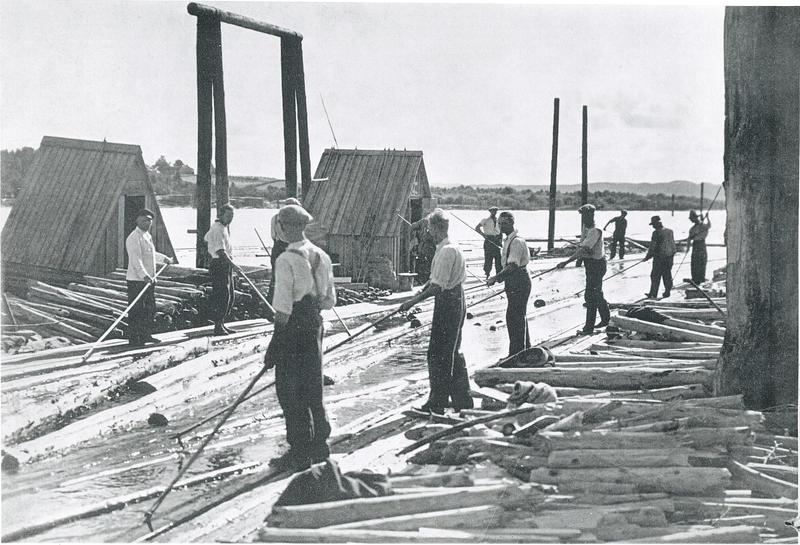 Historisk foto av personer som sorterer tømmerstokker ute på elva.