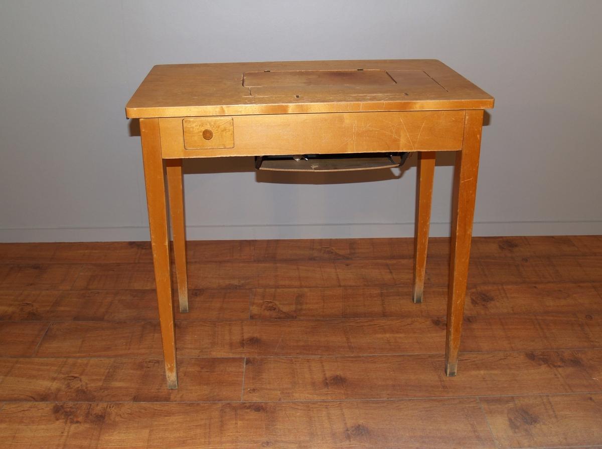 Symaskin fastmontert i et bord, der den henger under bordet i en egen hylle, når den ikke er i bruk. Når den skal brukes svinger man den opp i bordet og fester den.