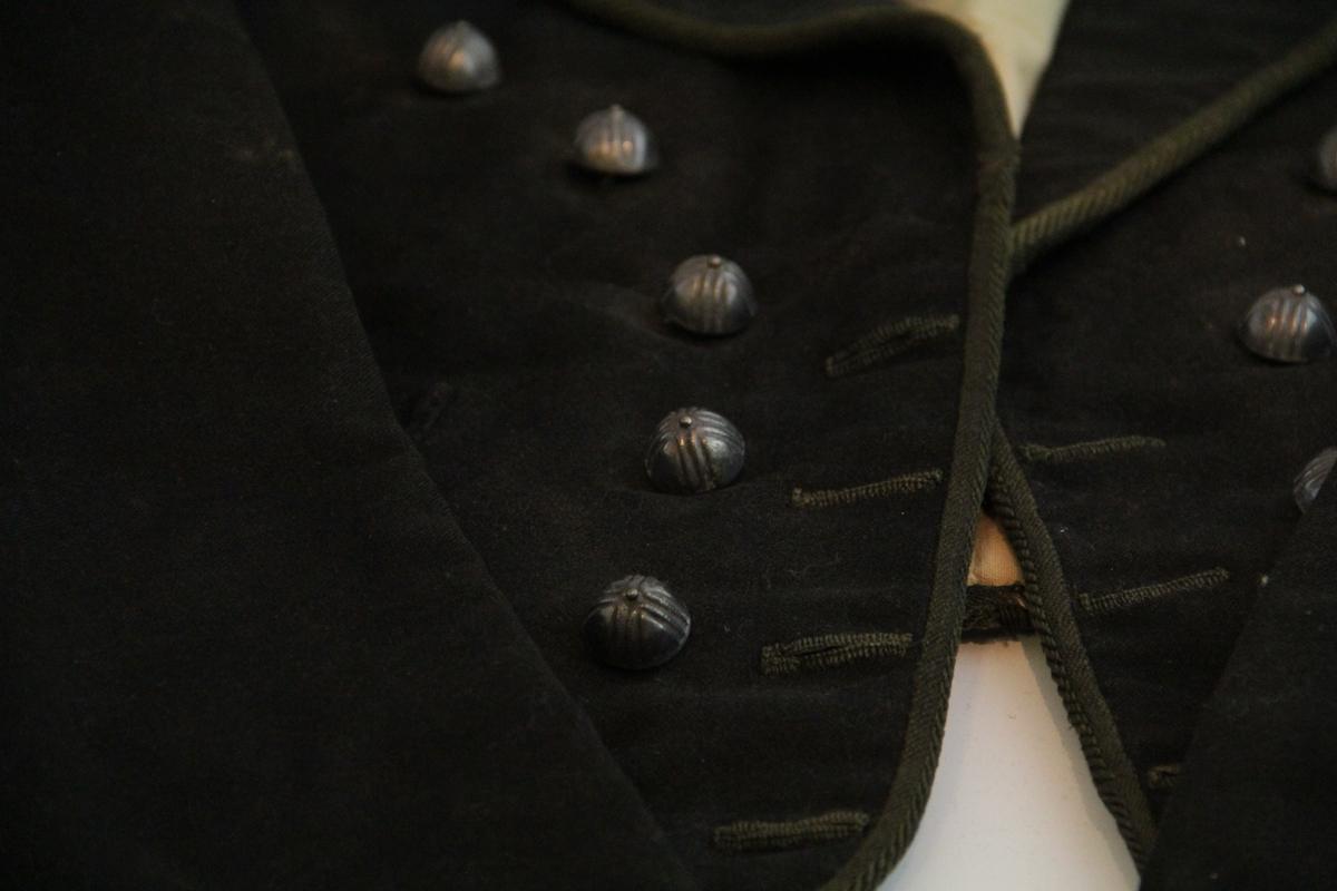 Jakke i mørkebrunt ullstoff. To knapperader, en på hver side, knapper i metall, halvkuleformet med uthevninger i kryssform og en liten knapp i toppen. Like, men mindre knapper nederst på mansjettene, to stykk på hvert erme, kun til dekor. Kraftig jakkeslag. To lommer i magehøyde, falske. Ekte lommer på innersiden av jakken. For i ubleket grovt stoff. Hempe for oppheng påsydd i nakken. Påsydd fabrikkprodusert kantebånd. Noe lengre foran enn bak. Ermene er skåret i C form i stedet for rett skåret. Håndsydd.
