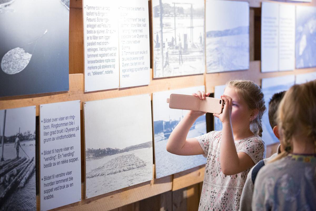 Barn som ser på utstilling av fløtingshistorie