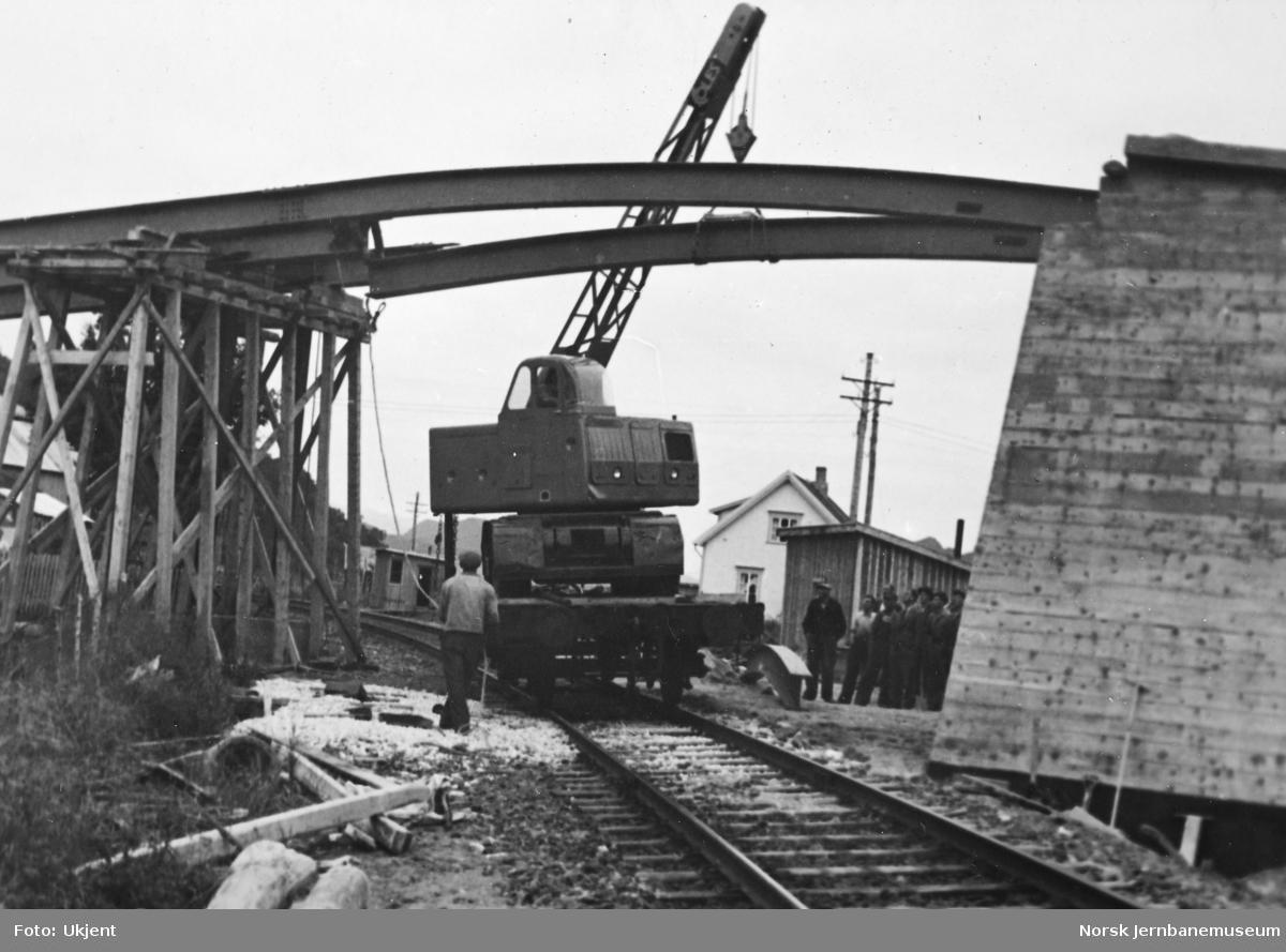Anlegget Mosjøen-Mo i Rana : bygging av bruovergang ved Halsøy, pel 200, Havnevesenets kranbil opplastet på jernbanevogn