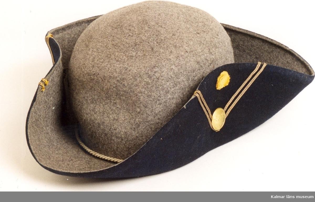 KLM 39700:2. Hatt. Uniformshatt. För löjtnant. Modell 1910. Av grått kläde. Yttre uppslag av blått kläde. Uppslagen häktas vid kullen med stor hyska och hake av gulmetall. Två rader beläggningssnöre bildar ett V på båda sidors uppslag. På vänster sida ovanför V gul kokard med två plisserade ringar, under kokarden mössknapp av gulmetall med tre kronor. Runt kullen, innanför uppviket, grå snodd. Två öljetterade lufthål på kullen bak. Ofodrad. Svettrem av brunt skinn, med handskriven text; Ågren. Kort remsa av grått kläde fastsydd på kullens insida.  Typen har även använts av frivilligkåren, den inkallade landstormen.