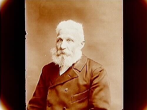 Äldre man med helskägg, bröstbild. Lars Gustav Wistrand född 1852 i Gällersta död 1927 i Nord Amerika.  Bodde i huset Sjölunda på Vinön.