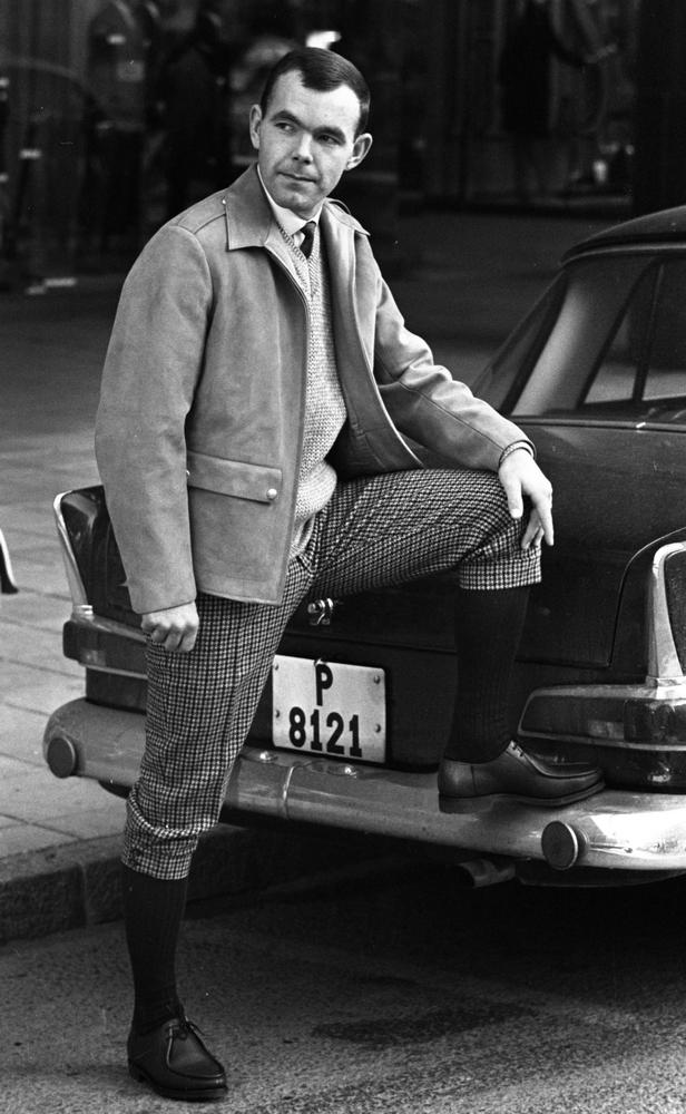 Höstmodet, 16 september 1965Höstens herrmode visas hos Bengt Nordins modebutik. I år skall det vara en blandning av amerikansk gangster och engelsk gentleman. Här visar modellen sig i mockajacka. slipover, rutiga tweedknickers, knästrumpor och svarta promenadskor.Han stöder vänstar foten mot bakre kofångaren på en bil med registreringsnummer P 8121.