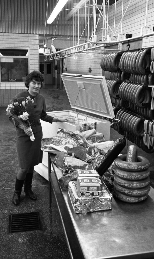 Orubricerat 18 februari 1966Kvinna med en blombukett i sin vänstra hand står i en charkuterifabrik. Bredvid henne står en frysbox. I förgrunden står ett bord fyllt med leverpsatej, korvar och fläskkött. Till höger hänger korvar i olika storlekar längs med väggen.