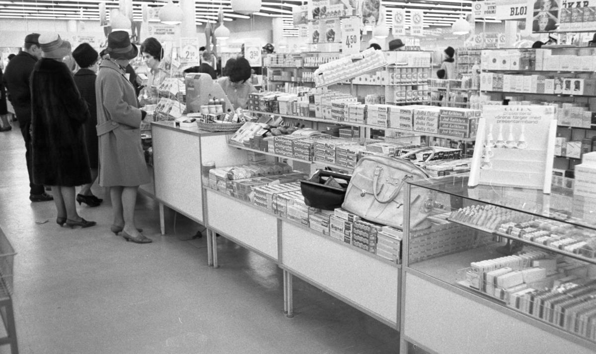 Väsktjuvar, Malmströms, Studenten 2, Väsktjuvar 20 april 1966I en affär står tre damer i hatt samt en herre och handlar vid disken. Bakom disken vid kassaapparaten står två kassörskor och betjänar kunderna. Två handväskor ligger bland varorna som i det här fallet råkar vara tandkrämstuber. Den ena handväskan är öppnad.