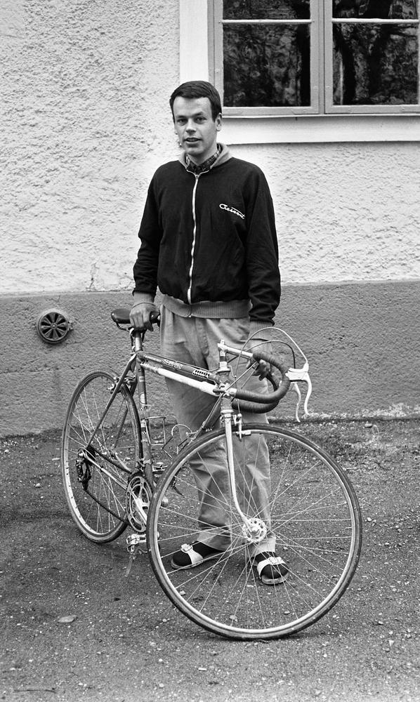 Palle Munther 18 maj 1967En ung man klädd i svart sportjacka med ljusa kanter, rutig skjorta, grå byxor, svarta strumpor och vita sandaler står och håller i en sportcykel.