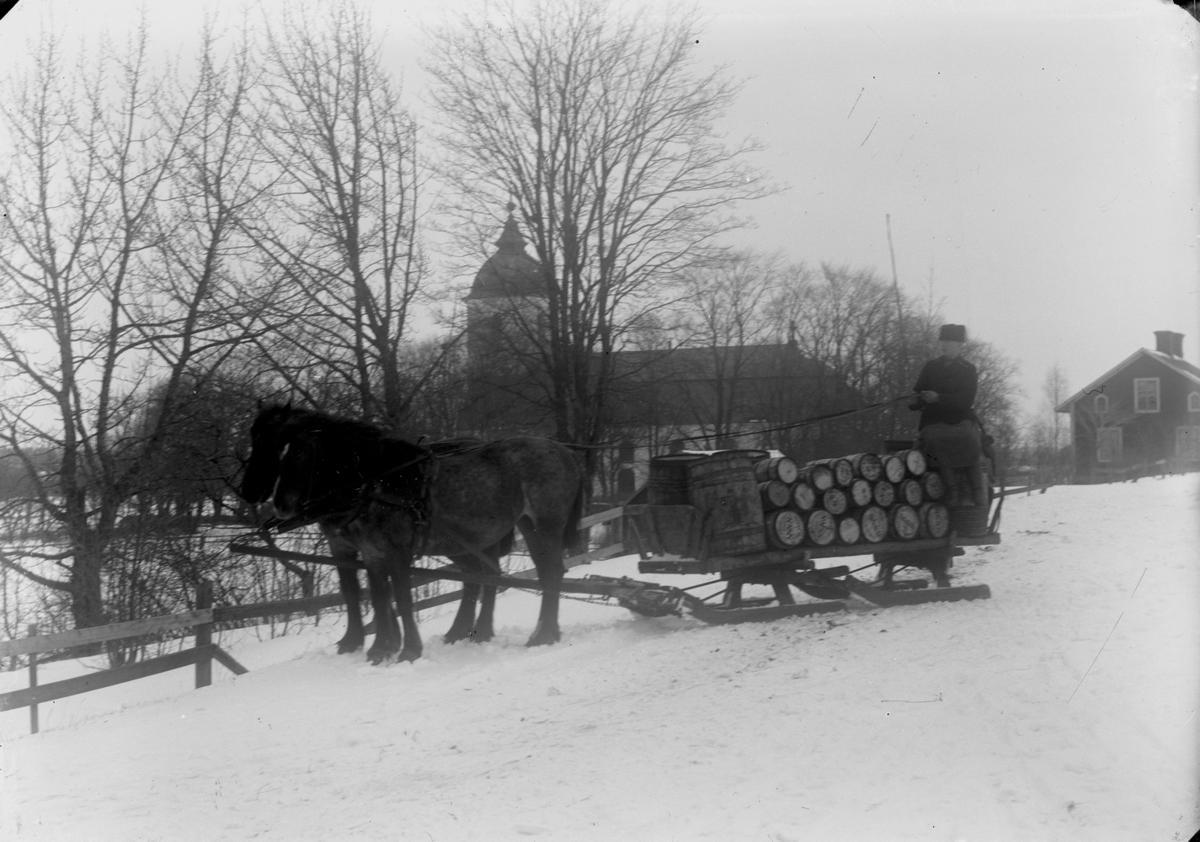 Två hästar spända för släde lastat med tunnor. En man.Svennevads kyrka i bakgrunden.