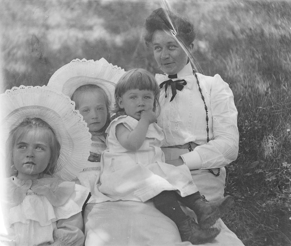 En kvinne sitter sammen med tre små barn i gresset. Den yngste sitter på fanget hennes.