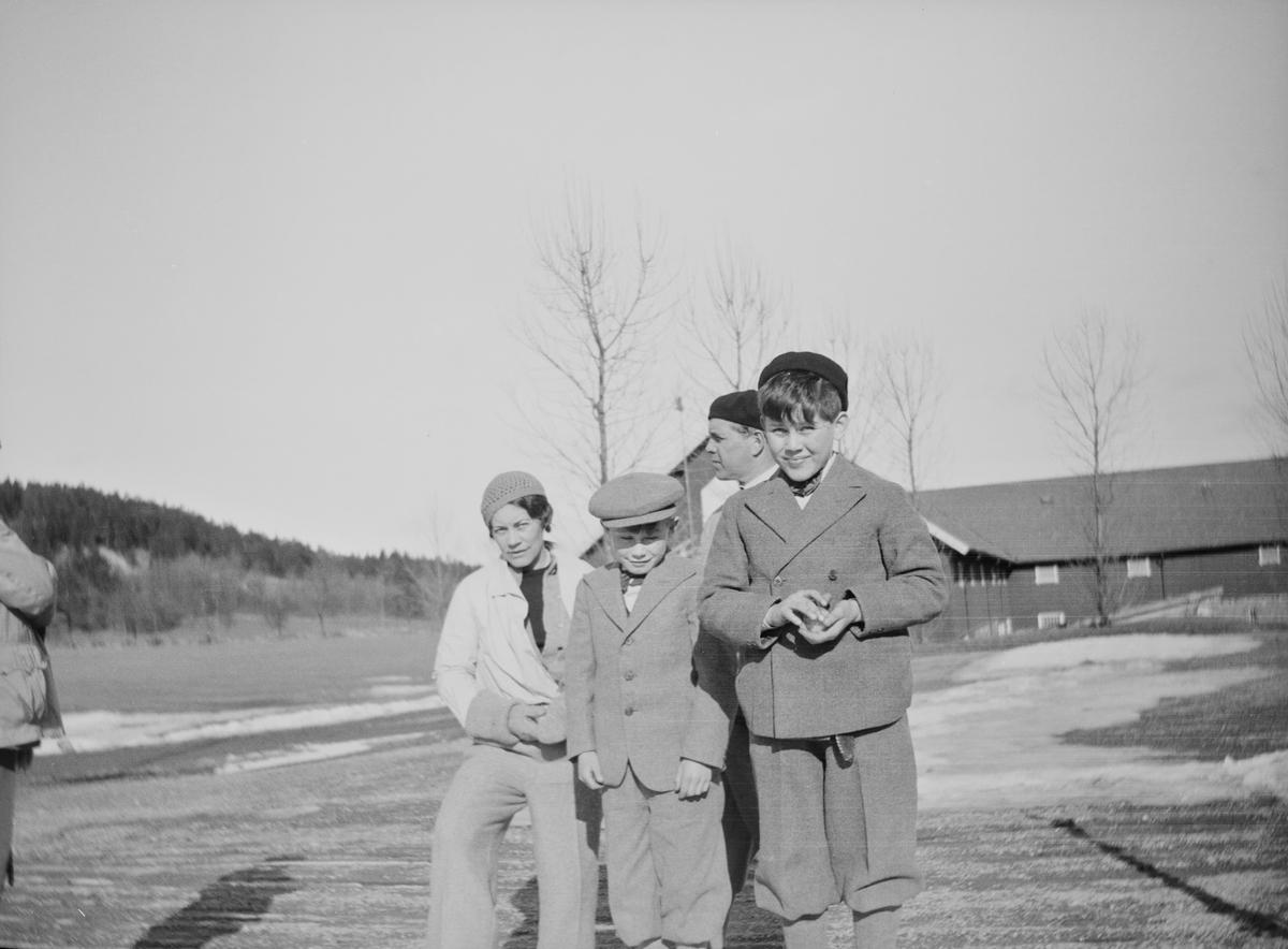 Celina Marie Mathiesen, en mann og to gutter har stilt seg opp for fotografen på gårdsplassen på Linderud gård. Den fremste gutten holder en snøball i hånden.