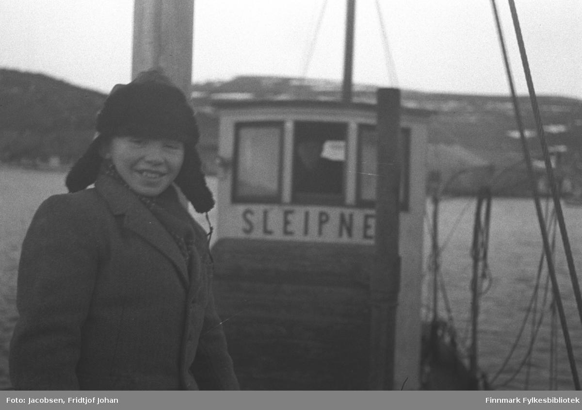En gutt/ung mann på dekket til fiskeskøyta Sleipner som var hjemmehørende i Revsneshavn i Kvalsund kommune og eid av Aksel Klemetsen. Han har en tykk, ganske mørk jakke på seg og en svart skinnlue med øreklaffer på hodet. Det forholdsvis lille rorhuset på båten er hvitt og navnet står med blokkbokstaver rett under de tre vinduene. Det midterste vinduet er åpent og et mannshode kan ses. Noe tauverk til høyre og bak på bildet er nok festet i mastene og rekka. Gutten står inntil formasta og en liten del av den kan ses bak han. Sjøen ser ganske rolig ut og noe diffust i bakgrunne ses et fjellparti og noen bygninger kan såvidt ses helt til høyre på bildet.