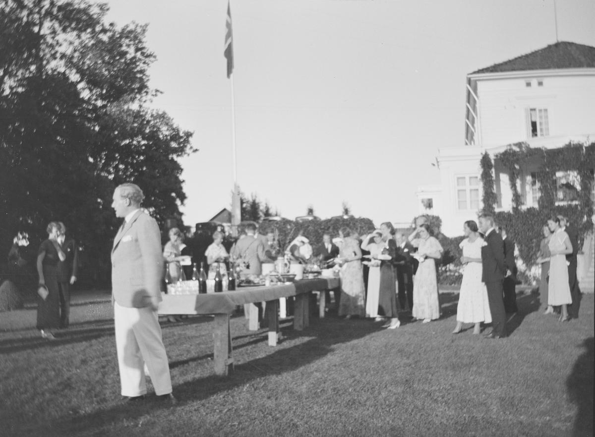 Det er selskap i den Victorianske hagen på Linderud Gård. Foran et bord med bl.a. drikkevarer og kvinner og menn kledd til hagefest , står Iacob Ihlen Mathiesen. Flagget er heist for anledningen.