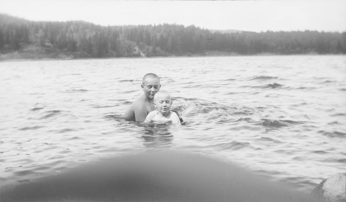 En eldre gutt hjelper en yngre gutt (trolig Iacob Ihlen Mathiesen) med svømmetrening i en innsjø på østlandet. Den yngste gutten har på svømmebelte.