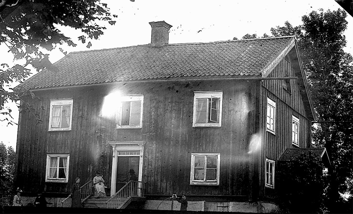 Bostadshus, några personer framför huset.