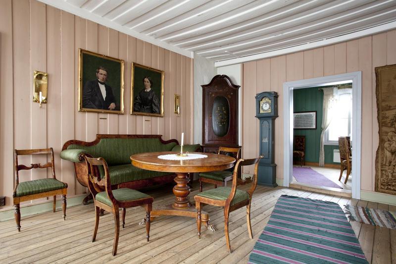 Spisestuen, med malerier av det siste presteparet Otto og Anne Margrethe Ottesen over sofaen.