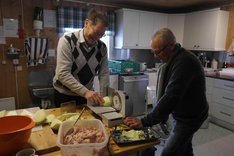 """to menn skjærer kål til surkålen som skal serveres på  """"Førjul på bygdetunet"""". (Foto/Photo)"""