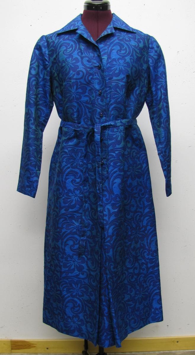 Klänningen är helskuren, i blommigt siden. Med lång ärm, krage och slag. Knäppslå med 5 knappar. Knytskärp.Tyget köpt av missionär Bo Reifors i Malaysia.