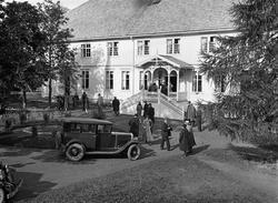 Personer og biler foran hovedbygningen på Rogneby øvre/Toten
