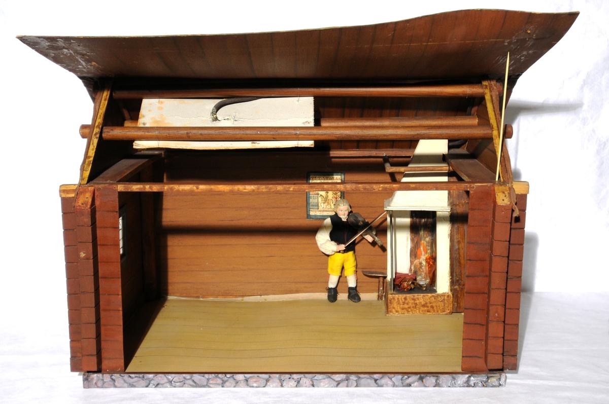 Dukkestue i form av svensk hytte med påmalte tømmerstokker, grunnmur og takstein i tegel. En vegg kan løftes bort og taket kan også åpnes. Stuen har tre stk vinduer med påmalte blysprosser. Inne i stuen er peis, bord og en dukke, en man i svensk folkedrakt med fele, fastmontert. På veggen henger et kurbitsdekorert maleri av Carl Johan.
