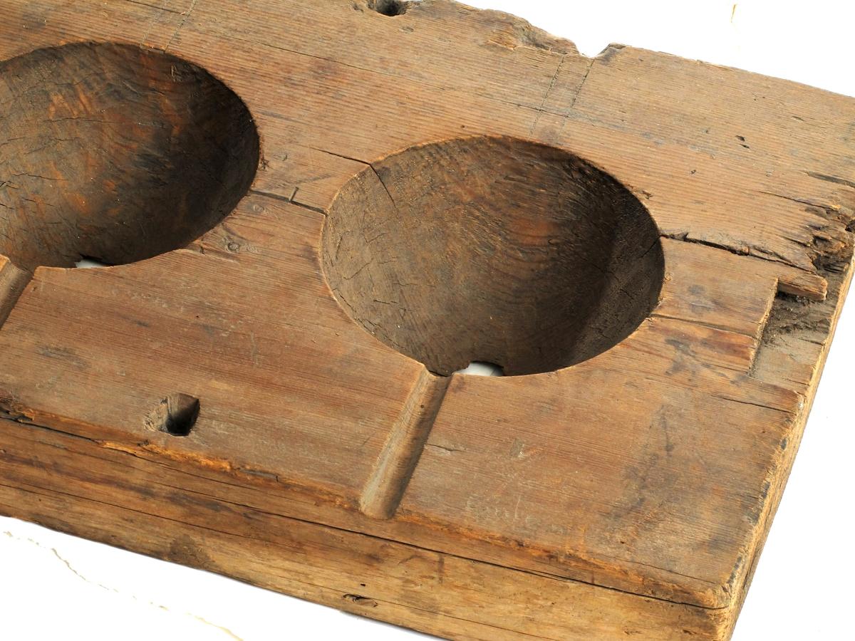 Støpeform for kanonkuler. Furu. Med 4 halvkuleformede fordypninger, hver med en smal :renne ut til ytterkant.