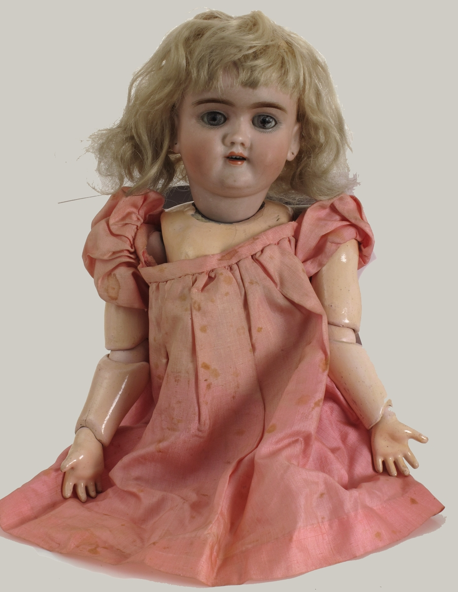 """Dukke. Hode av porselen, med øyne som lukkes når dukken ligger, med lyst hår. Kropp av pappmasjé  påtrykt  Handwerek""""."""