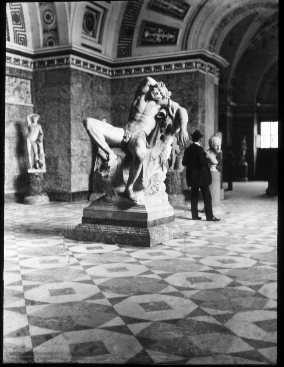 Skioptikonbild från institutionen för fotografi vid Kungliga Tekniska Högskolan. Motiv föreställande en skulptur den Barberinska faunen, glyptoteket i München, Tyskland. Bilden är troligen tagen av John Hertzberg under en resa i Europa.