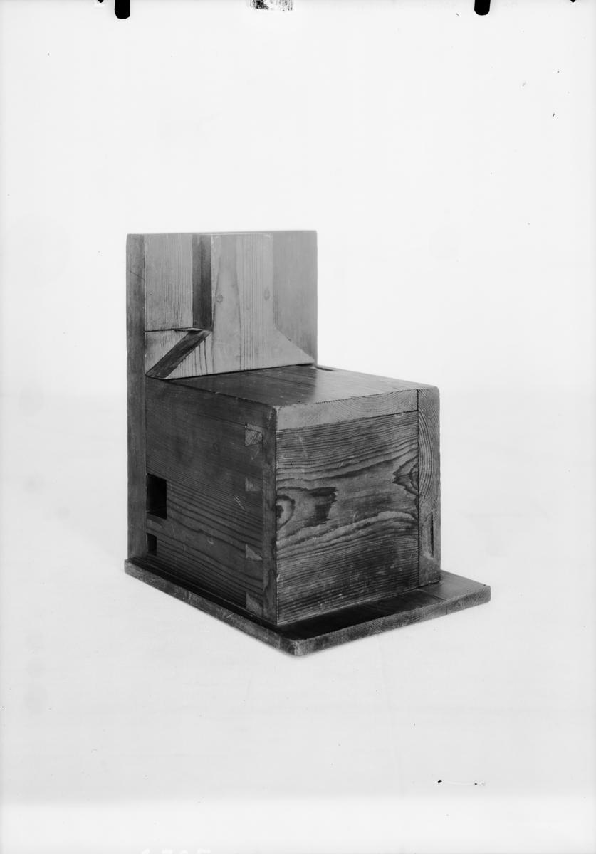 """Modell av bakugn. Text på föremålet: """"D. (?)"""". I Jonas Norbergs förteckning från 1779 beskrivs modellen på följande sätt: """" Modell på Spisell, med bakugn och torkställe der ofvanuppå, inventerad af Undertecknad [J. Norberg] til tarflige hushålls behof, der man efter landtmaner, har bakugnen inne uti boningsrummet# denne bakugn har sin särskilte eldningsugn, hvarifrån värmen går både under och öfver bakugnen, så att denna senare aldrig behöfver sopas, utan kan oafbrutit nyttjas til brödets bakning. Spiseln är gjord som en liten kjöksspis, hvarifrån då kokningen är skedd, den öfrige elden skyflas in i eldningsugnen, at der brinna ut, lika som i en kakelugn. Men då man intet behöfver koka, utan eldar blott för at värma rummet, då lägges veden straxt in uti eldningsugnen, hvars öppning är inuti spisen, hvarifrån värmen dunstar in uti rummet vid bakugnen hvilkens mynningar är på ena sidan om spisen."""""""