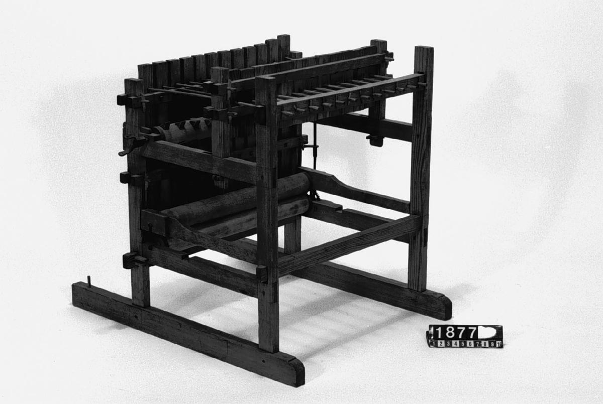 """Modell av tröskverk. Text på föremålet: """"N:o 52"""". I Jonas Norbergs förteckning från 1779 beskrivs modellen på följande sätt: """" Modell på Trösk Machine med stampar, at drifvas medelst strömfall, gjord af underteknad [J. Norberg], med åtskillige förbättringar. I synnerhet är densamma så inrättad, att om än vatnhjulet ligger aldrig så djupt ned i strömmen, Så står ändå tröskmachinen uppe på jämna marken# och dess kuggevalts som lyfter stamparna, blir medelst en särskilt invention omkringdragen af en, (45 grader eller något mindre) över vatnhorizonten lutande smal stock, som går ner til vatnhjulaxeln såsnart sädeskornen komma lösa utur axen, rinna de straxt ned uti en, under det gående halmlaget belägen, igenlåst brädlår, så at ingen uttröskad säd, kan af otrogit folk bortstjålas. Kunna stångren, på hvilka stamparna hänga, hvar för sig, medelst kilar spännas högre eller lägre, alt som det fordras, på det at stamparne efter slagen icke må hindra det framskridande sädesslaget, och at stångren må lagom trycka stamparna."""""""