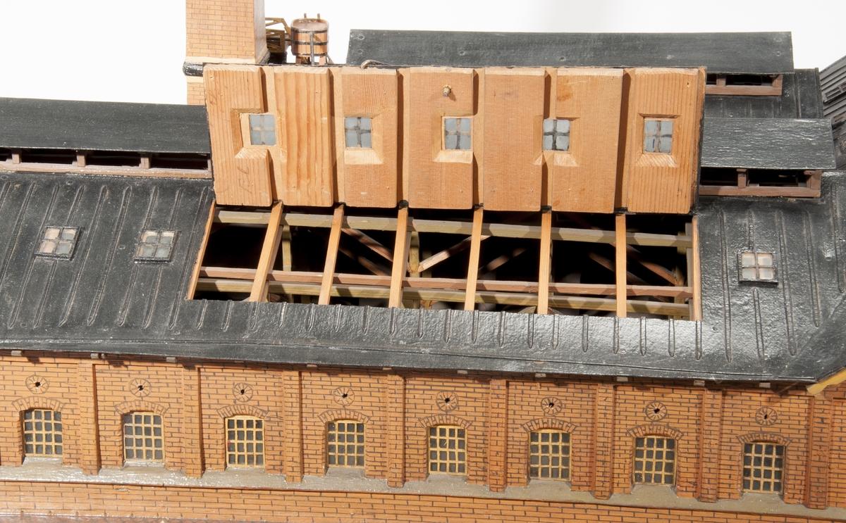 Modell av kopparextraktionsverk av trä och glas. Föremålet föreställer en fabriksbyggnad med hög skorsten inkl. rökmoln. Ett lätt ånglok med fyra malmvagnar ingår. Tillbehör: Glasmonter.