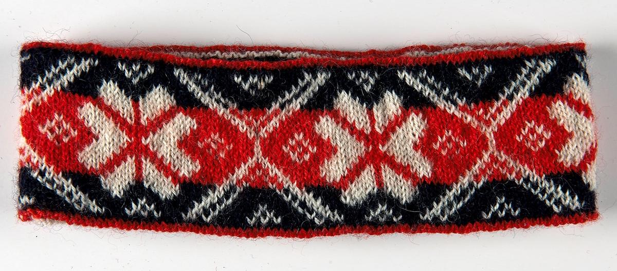 """Pannband i 2-trådigt ullgarn. Pannbandet är resårstickat med m blått garn på insidan och slätstickat med rött,blått och vitt garn i mönsterbården """"Laholmsblomman"""" på utsidan."""