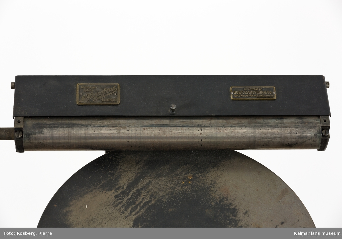 KLM 45377:60. Tryckpress, Trä och metall. Digelpress av svartmålad metall, stommen av gjutjärn. På digelpressens övre del sitter två metallplåtar. På den ena plåten står det Maschinenfabrik A Hogenforst Leipzig. På den andra står det Importerad av Gust. Carlsson&Co Maskinaffär Stockholm. Digelpressen är monterad på ett litet träbord som förmodligen är byggt för pressen. Det är delvis målat i vitt.