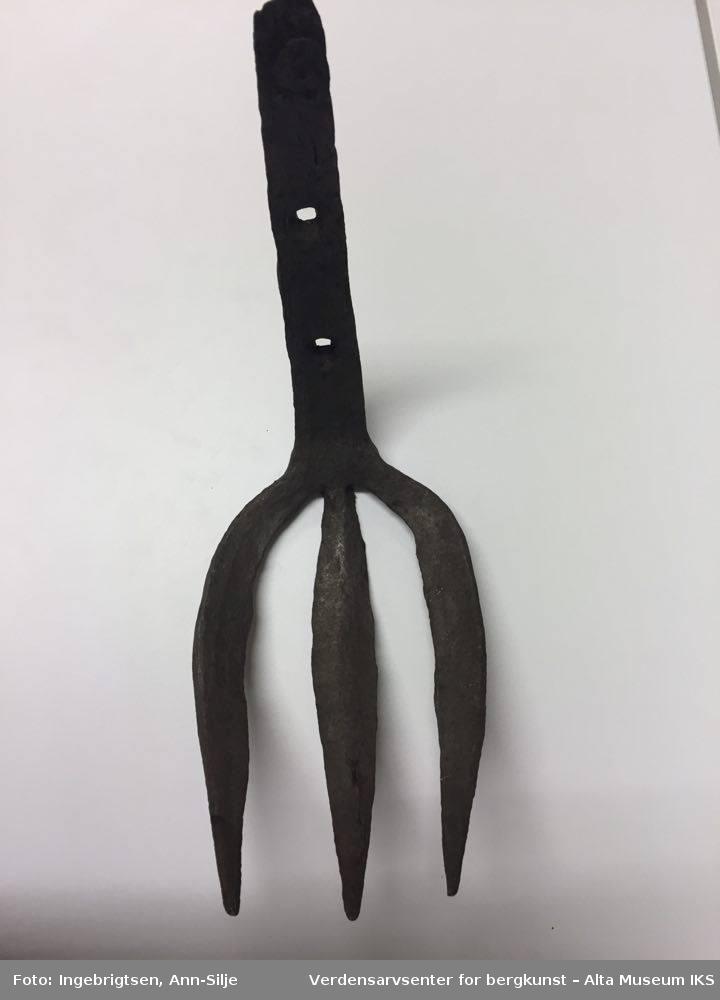 """Trearmet jerngaffel. Kort skaft i samme metall. Liten krok på baksiden øverst på skaftet. To hull i skaftet (3 cm mellomtom). Hver av """"armene"""" er ca. 20 cm lange. Skaftet er 23 cm langt."""