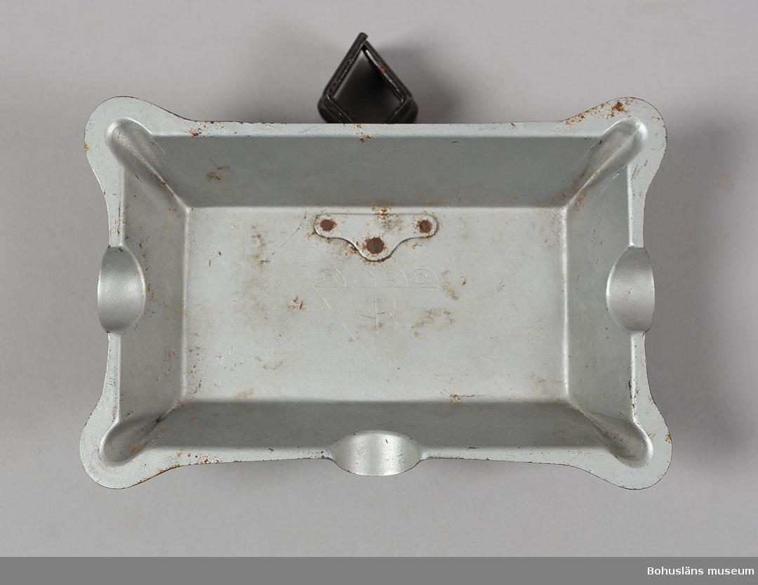 Rektangulär askkopp av pressad  silverfärgad metall. Fatet kläms fast direkt på tältstången med en svartlackad klämma.  Askfatet sammanhör med tält med brutet tak, UM27693:1. För ytterligare upplysningar om förvärvet, se UM27693:1 och insamlingen UM27670.