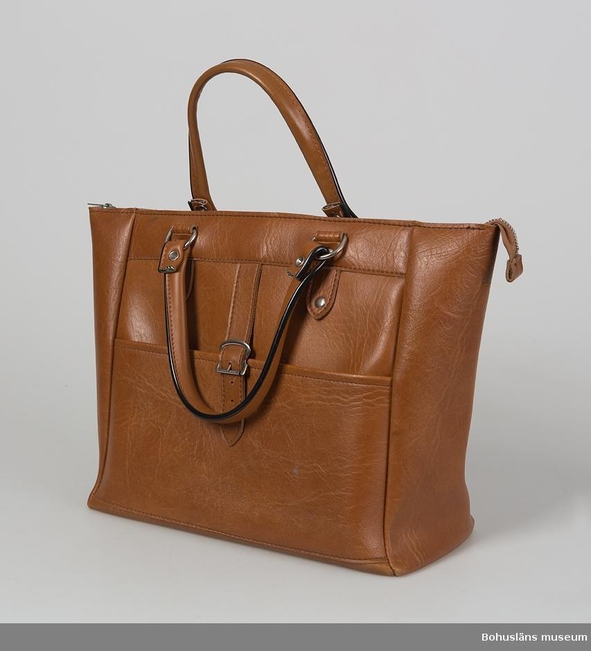 Kvadratisk handväska av ljusbrunt läderpressad galon med  effektstickningar i beige. Två korta handtag med svart kantdekor, fastnitade på resepktive långsida, fästade i metallöglor som i sin tur sitter fästade via fastnitade och fastsydda remmar. Väskan öppnas genom dragkedja, ficköppning på ena långsidan som kan stängas genom rem med bältesbeslag. Inuti ofodrad med fastsydd innerficka i konstläder samt brun, präglad bottenpapp. Fläckar på insidan. Väskan är i gott skick.  För ytterligare upplysningar om  insamlingen, utställningen 2001 och litteratur, se UM027670.