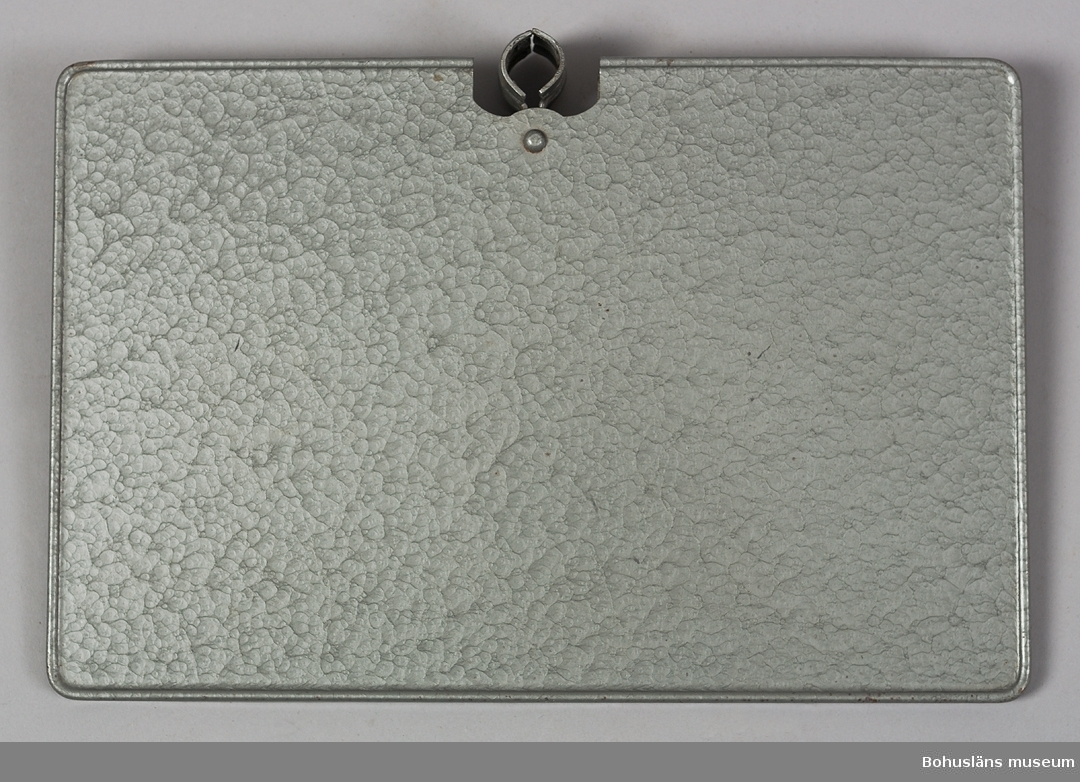 Tältbord av grålackerad metall. Bordsskivan kläms fast direkt på tältstången och passar stänger upp till 22 mm. Undertill med fjäderbelastad klämma. Bordsskivan  sammanhör med tält med brutet tak, UM027693:1.  För ytterligare upplysningar om förvärvet, se UM027693:1 och insamlingen UM027670.