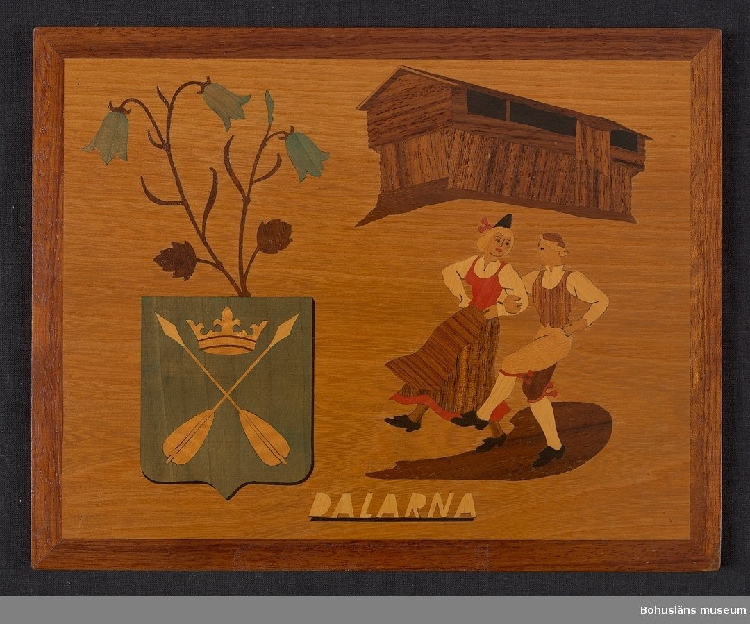 """Landskapstavla med namnet DALARNA med landskapsvapnet, två korslagda dalpilar krönta av en hertiglig krona. Ikoniska motiv typiska för landskapet inlagda i intarsiateknik av fanér i olika ljusa och mörka träslag.  Några mindre bitar är infärgade i grönt (från början troligen blått) och rött.  Lackad.  Motiven avbildar blommande blåklocka, Ornässtugan och en dansande kvinna och man i folklig dräkt. Intarsian är skuren så att träets naturliga mönster skickligt medverkar till och understryker motivens former och volymer.  Beskrivande etikett av papper på baksidan med texten: Landskapstavla """"DALARNA"""". Motiv: Vapnet, Blåklocka, Ornässtugan, Daldans.  Träslag: Alm, Ostindisk jakaranda, Böbinga, Guarana, Amerikansk valnöt, Lönn, Ybam, Blå färgad lönn m. fl. . Komponerat av: Konstnär B. Ekman. Tililverkad av Bohus Intarsia, Uddevalla.   På baksidan en upphängning."""