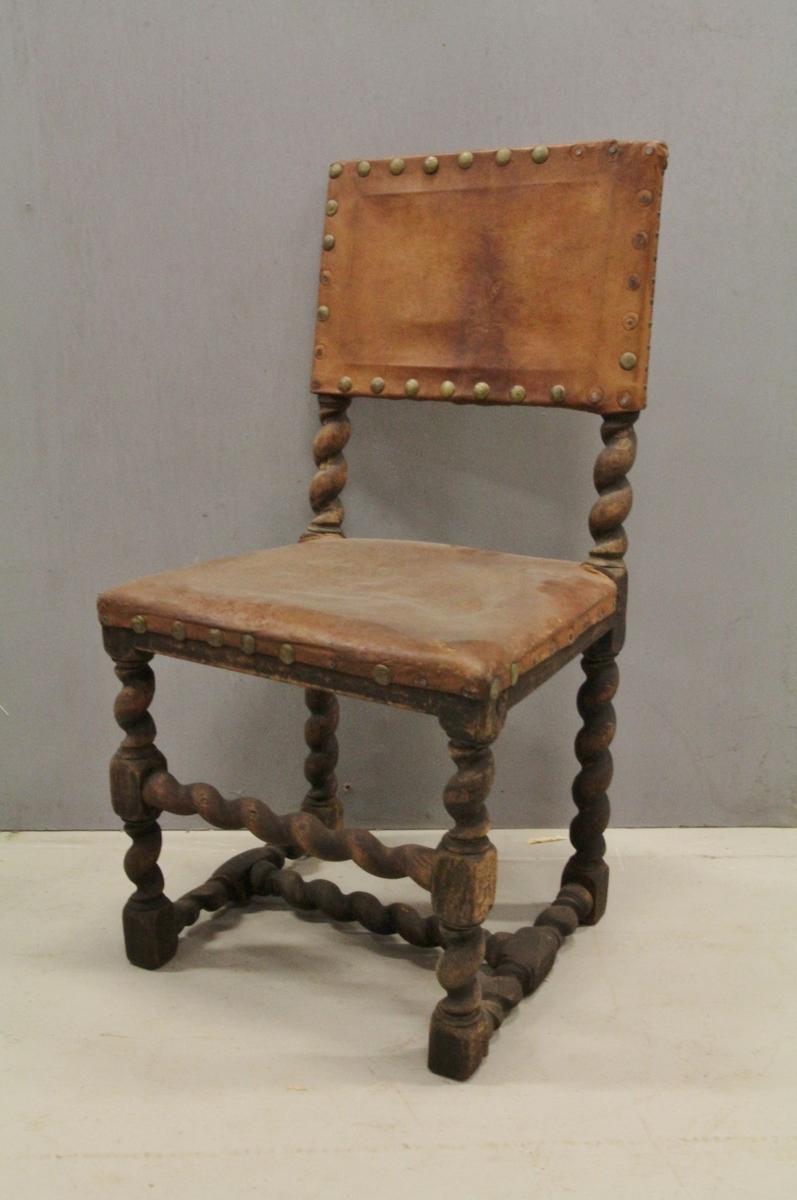 Trestol med skinntrukket sete og rygg. Beina rette med slynget fasong (ligner spiralsøyle), forbundet med H-sprosse og 1 vertikal sprosse foran (også spiralsøyle formet). Skinnet er naglet fast til treverket.